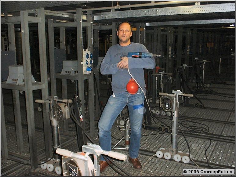 Foto 20-398. John Lankreijer op de lichtvloer; met boormachine.De bal voorkomt dat het gereedschap 9 meter naar beneden kan vallen